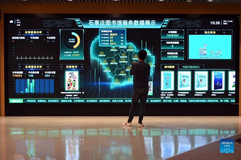 A man watches service data displayed on a giant screen at the Shijiazhuang Library in Shijiazhuang, capital of north China's Hebei Province, Oct. 6, 2021. The library hosted a series of cultural events to better entertain visitors during the week-long National Day holiday starting from Oct. 1. (Xinhua/Luo Xuefeng)