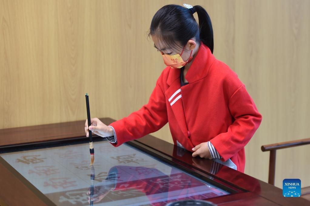 A girl practices Chinese calligraphy on an electronic device at the Shijiazhuang Library in Shijiazhuang, capital of north China's Hebei Province, Oct. 6, 2021. The library hosted a series of cultural events to better entertain visitors during the week-long National Day holiday starting from Oct. 1. (Xinhua/Luo Xuefeng)