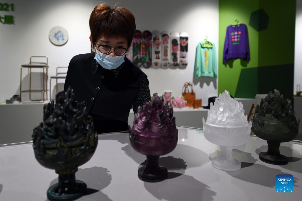 A woman watches cultural and creative products displayed at the Shijiazhuang Library in Shijiazhuang, capital of north China's Hebei Province, Oct. 6, 2021. The library hosted a series of cultural events to better entertain visitors during the week-long National Day holiday starting from Oct. 1. (Xinhua/Luo Xuefeng)