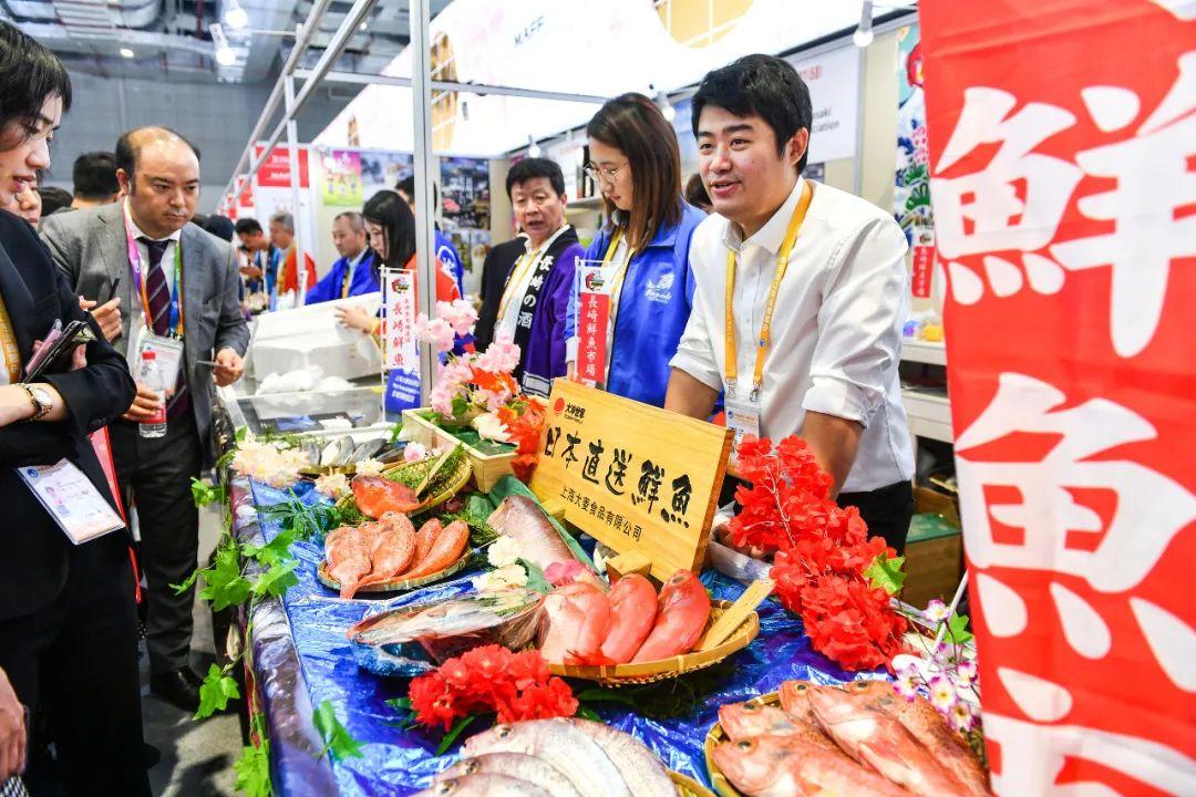 """▲资料图片:2019年11月6日,上海,第二届中国国际进口博览会上,来自日本各地的中小食品企业组团在进博会食品展馆里建了一条""""美食街"""",受到观众热捧。图为一家海产品店正在出售鲜鱼。(视觉中国)"""