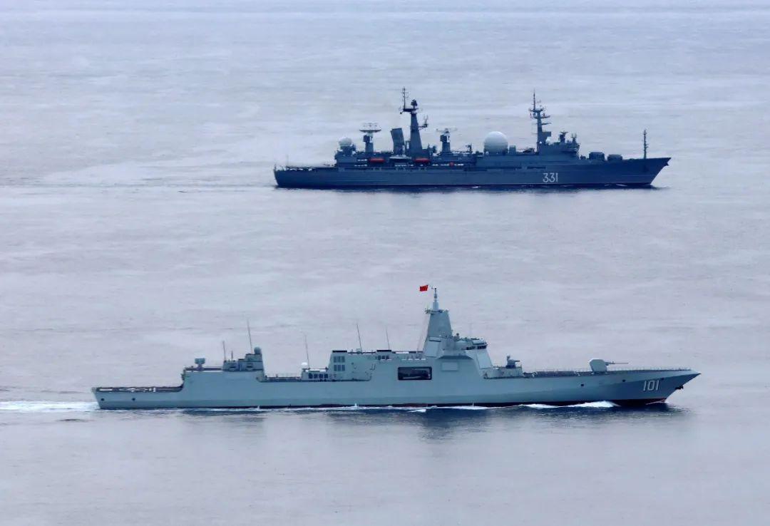 """▲当地时间10月19日,参加中俄""""海上联合-2021""""军事演习的巡航舰艇编队在西太平洋海域联合航渡。这是中国海军南昌舰(下)与俄海军""""克雷洛夫元帅""""号指挥舰。新华社"""