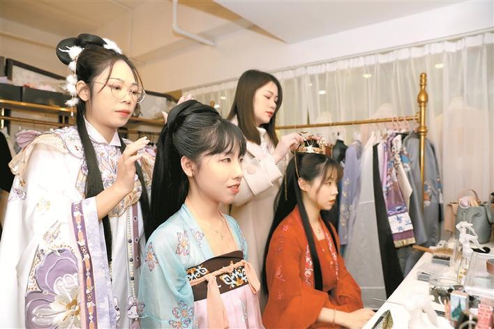 ▲钟美华(后排右)和同事在为顾客设计妆容。深圳晚报记者 张焱焱 摄