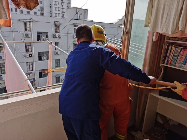 晾衣杆被风吹歪悬在半空 消防队员上门援助