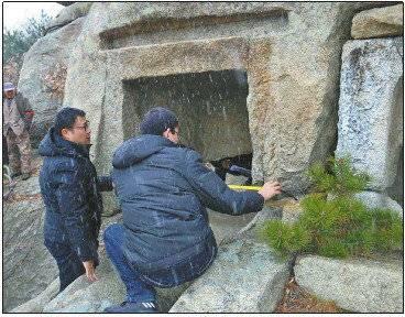 调查工作人员在烟台市牟平区连环盆石窟冒雪测绘。
