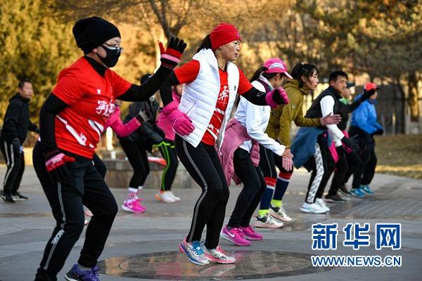 """1月1日,在宁夏银川市森林公园,跑友在完成""""打卡""""后活动拉伸。"""