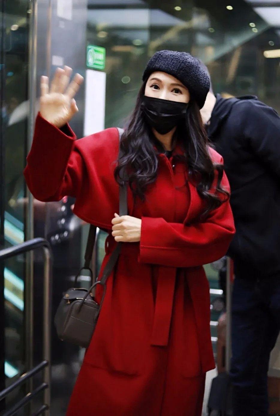 伊能静穿红大衣走机场,踩高跟长靴,打扮这么时髦不像老人!