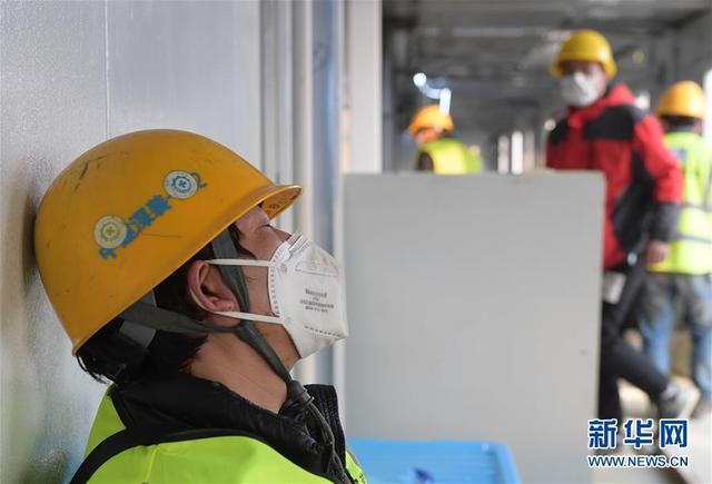2月3日,一名疲憊的工人在武漢火神山醫院工地一處正在施工的病房外小憩。 新華社記者 李賀 攝