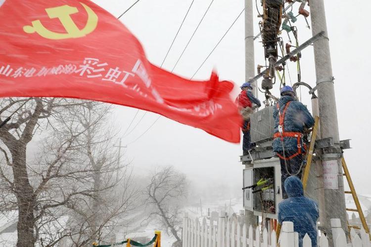 """(国网威海供电公司工作人员顶风冒雪更换为变压器,保障""""煤改电""""村庄取暖用电 刘中华 摄)"""