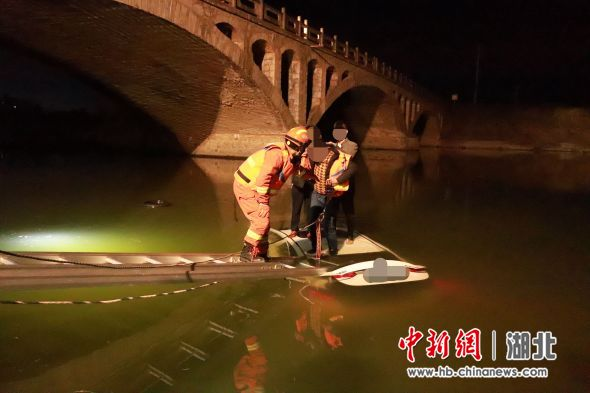 湖北十堰:轿车不慎坠河 司乘人员车顶待援获救