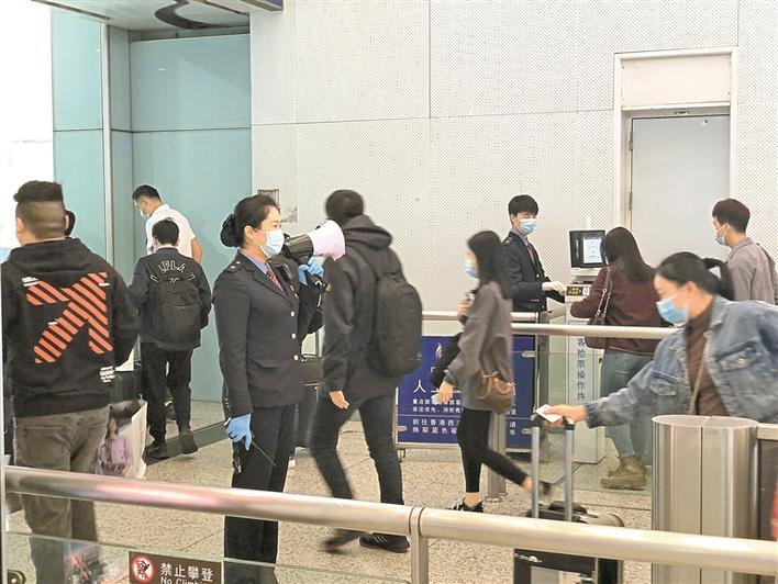 客运员王珂在检票口提醒旅客戴好口罩。深圳晚报记者 邱志东 摄