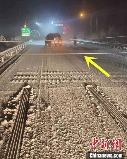 箭头所指为脱落后阻断高速公路的高压电缆。图中可以看出,有些车辆因路面积雪,紧急制动时轮胎拖出长长的印痕。高速交警供图