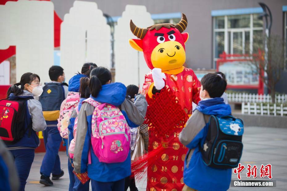 """3月2日,山西省太原市小学四至六年级开学。新建路小学总校区三位""""80后""""教师身着""""福牛""""服装,接学生们有序入校。 中新社记者 张云 摄"""