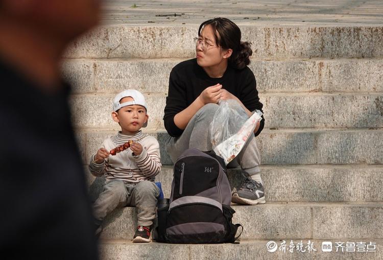 千佛山公园庙会上,一名小朋友吃着糖葫芦