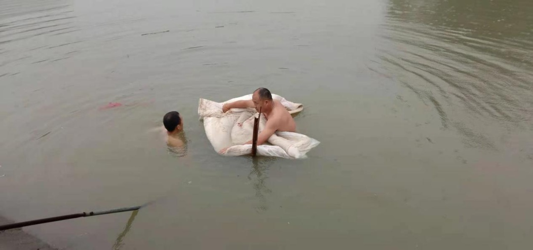 池塘漏水,湖南一对父子跳入水中用棉被和沙子堵住缺口