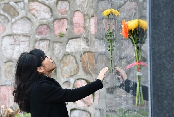↑2017年4月1日,抗日航空义士汤卜生的孙女汤伟华在南京抗日航空义士怀念碑广场上刻有汤卜生名字的怀念碑上粘贴菊花。新华社记者孙参摄