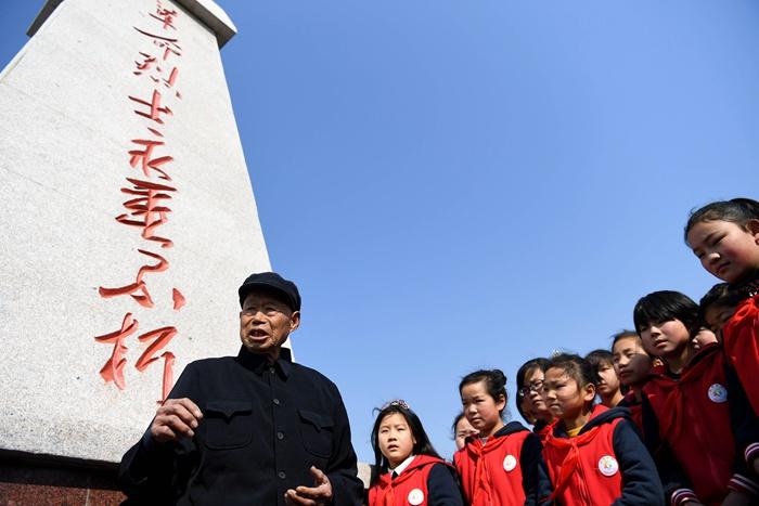 安徽省怀远县陈集镇胡刘义士陵园治理员,70多年如一日为英烈们守墓。这是他在义士陵园为前来省墓的小门生解说义士的古迹(2019年3月14日摄)。新华社记者刘军喜摄