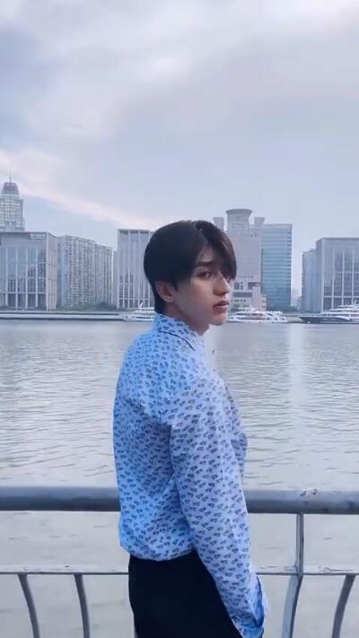 蔡徐坤清晨江边营业 清新蓝衬衫搭配烟管裤视觉2米8