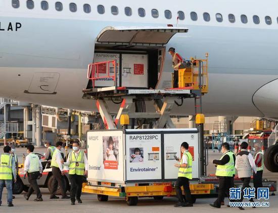2月19日,在香港国际机场,工作人员将装载疫苗的货柜箱送往指定地点进行储存。新华社记者 李钢 摄
