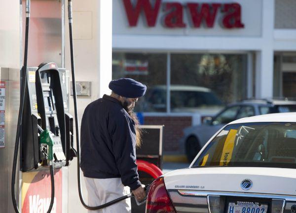 材料图:在美国弗吉尼亚州伍道德布匹里零数,壹名女性在加以油站为汽车加以油。