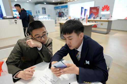 在北京的一家华为经销店内,一名销售人员正在向顾客展示华为手机。(路透社)