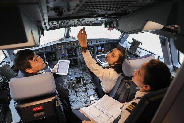 资料图:在重庆江北国际机场,飞行员在驾驶舱内进行起飞前检查。