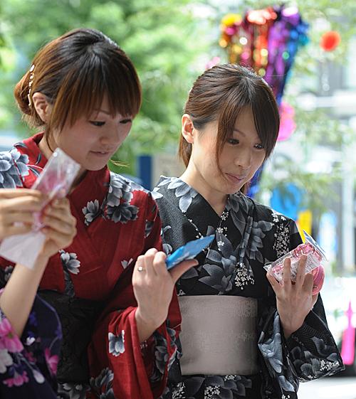 在日本首都東京街頭,穿着夏季和服的女孩選購物品。(新華社)