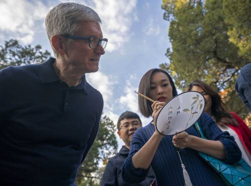 圖爲在北京孔廟,一名蘋果手機愛好者爲蘋果公司CEO蒂姆·庫克展示在扇面上寫毛筆字。新華社