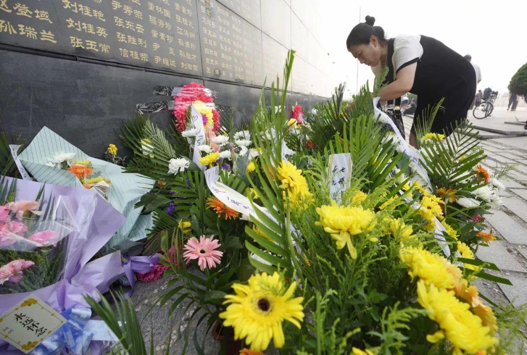 2018年7月28日,唐山大地震42周年纪念日,人们来到唐山大地震纪念墙前,摆放鲜花,祭奠亲人。新华社发(董钧 摄)