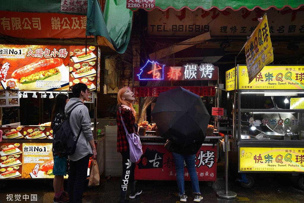2018年11月26日,臺北,一個女孩在士林夜市等商家制作自己的小吃 @視覺中國