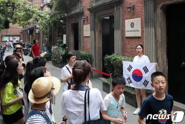 14日,一名韓國女游客在臨時政府舊址前舉太極旗留念。(news 1)
