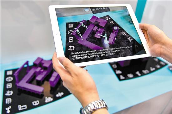 """工业互联网应用场景特色展广州开展。图为工作人员展示""""5G+AR""""工业应用 视觉中国供图"""