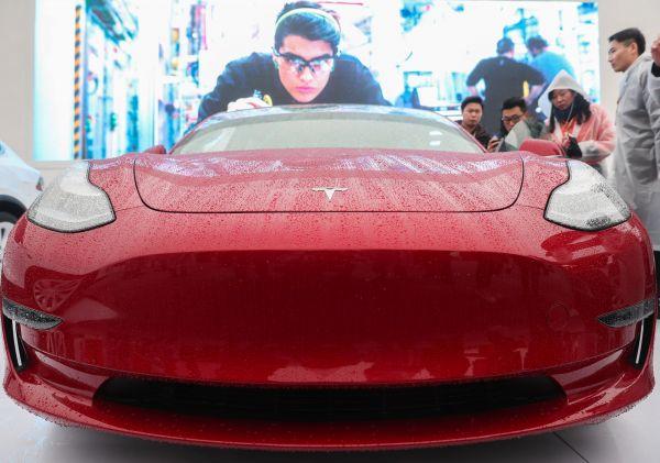 资料图:人们在特斯拉上海超级工厂(一期)奠基仪式现场观看展出的Model 3车型。 (新华社)