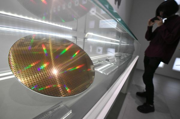 資料圖片:一名參觀者在首爾三星電子的展示廳內觀看製造出來的晶圓。(法新社)
