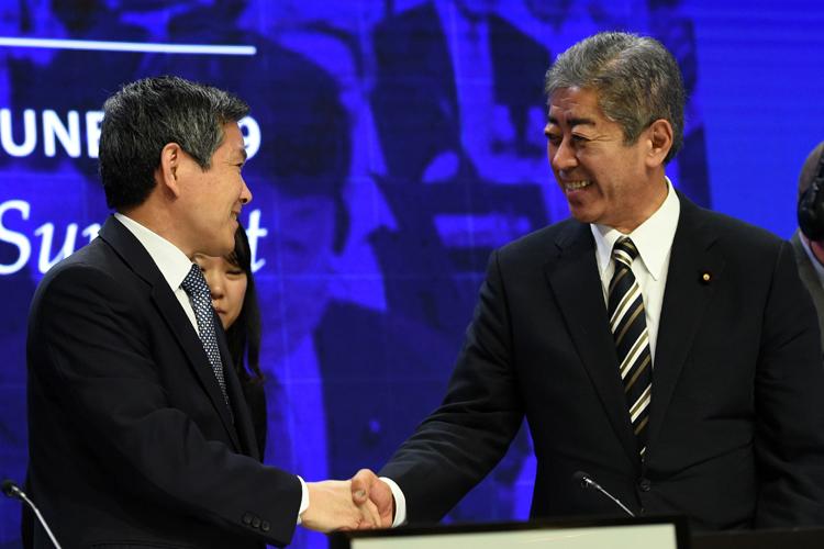 日本防衛相巖屋毅與韓國防長鄭景斗微笑握手,遭到批評(法新社)