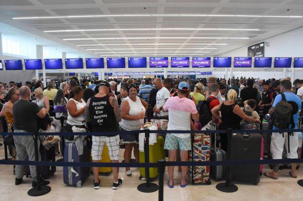 9月23日,朱西哥坎昆国际机场内,游客正在封闭的托马斯·库克公司值机柜台前排起少队。(新华社/法新)