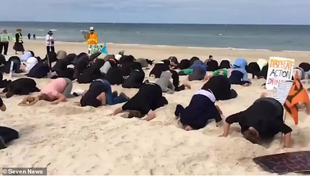 一群澳大利亚人跪在海滩上,把头