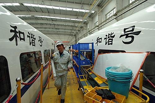 """2007年4月12日,在南车四方机车车辆股份有限公司,工人在为""""和谐号""""CRH动车组进行车体安装。(新华社)"""