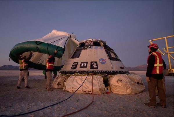 工程师们检查落地后的太空舱并准备为太空舱架起帐篷 图自 NASA官方网站