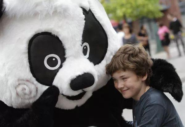 """▲资料图片:2015年8月,在加拿大温哥华,一名小男孩与唐人街吉祥物大熊猫""""威威""""拥抱。(新华社)"""
