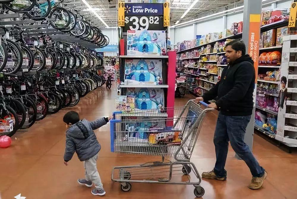 11月29日,在美国宾夕法尼亚州,一名儿童跟父亲逛沃尔玛的玩具区。新华社/路透