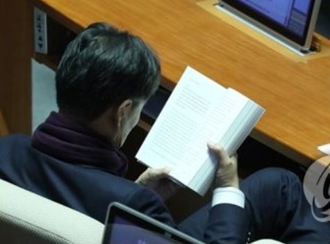 强打精神,看会儿书(韩联社)