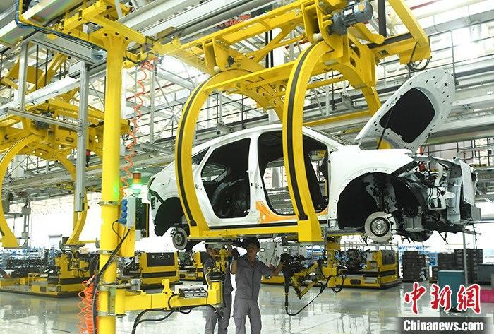 资料图:一汽车生产车间内的工作人员正在组装车辆。 中新社记者 陈超 摄
