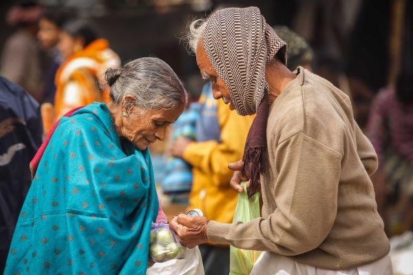 资料图片:印度西孟加拉邦,两名老人在集市购物。(新华社)