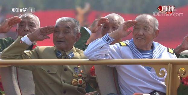 """△吴洪甫(左二)在庆祝中华人民共和国成立70周年大会群众游行活动中,应邀坐上""""致敬""""方阵的20号礼宾车。"""