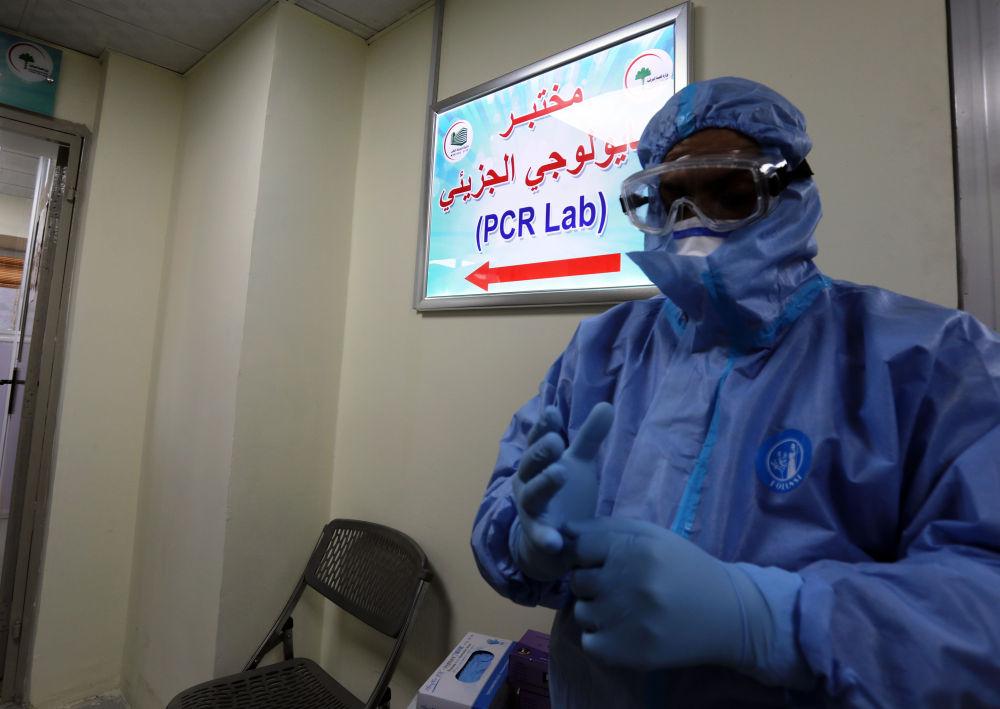 3月30日,在伊拉克巴格达,中国援建伊拉克的核酸检测实行室卖力人穆罕默德·迈赫迪穿着防护服预备事情。新华社发