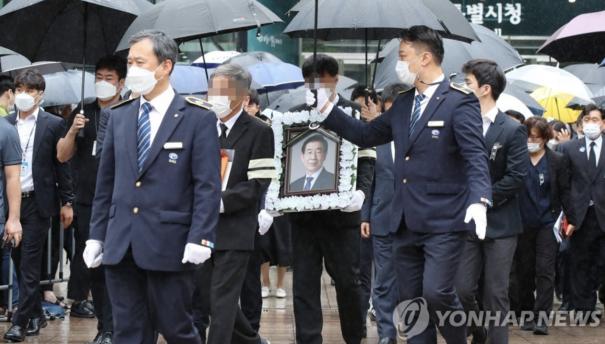 △13日上午,在首尔市政厅,朴元淳的遗属捧着遗像到达遗体告别仪式现场。图片来源:韩联社