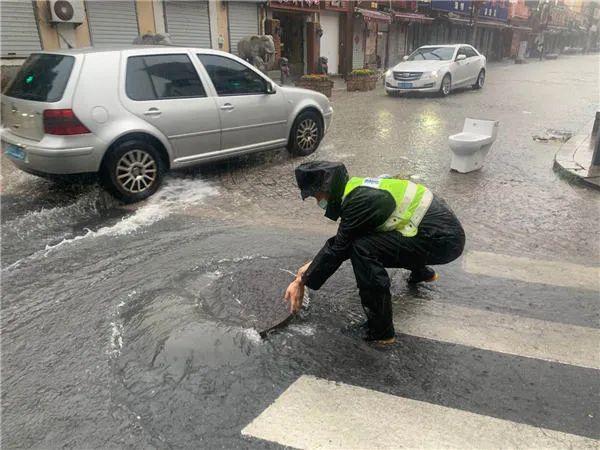 △市南交警打开井盖加快排水。