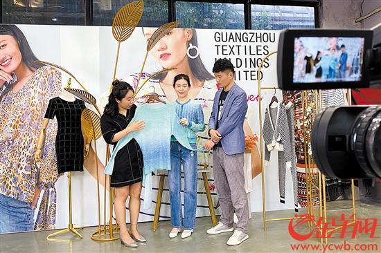 """广州纺织品进出口有限公司的工作人员在广交会""""云上""""直播间展示商品"""