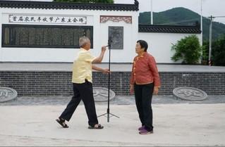 图为廖胜华配偶在大黄村丰收广场手机直播。(人民网史新培 摄)