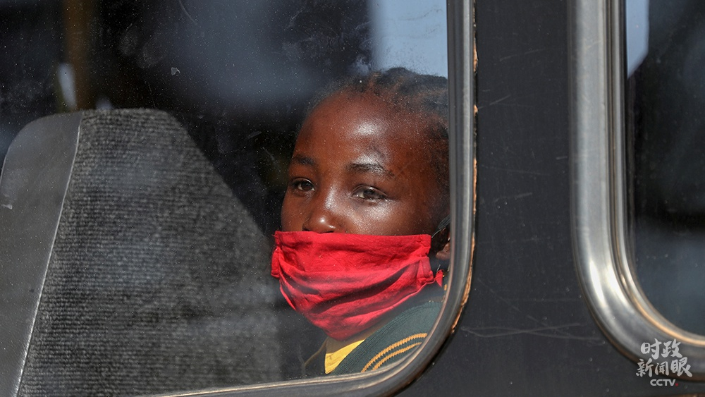 △南非约翰内斯堡,公交车里向外观望的女孩。